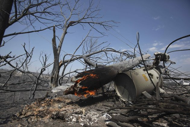 A power line pole and transformer smolder in an area destroyed by a wildfire at Possum Kingdom Lake, Texas, Wednesday, Aug. 31, 2011. The wildfire that swept through the neighborhood on Tuesday, one o