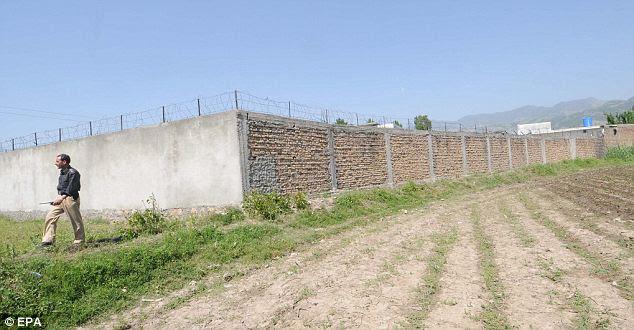 Alta: Um oficial de segurança paquistanês passa, o composto de Bin Laden