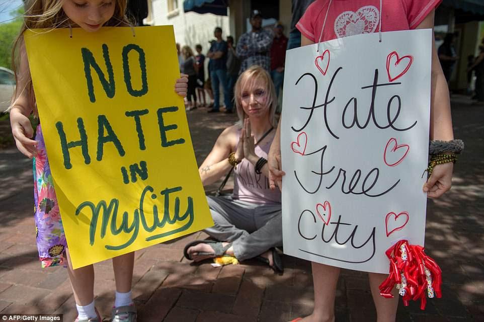 Residentes de Newnan October Strange (izquierda), seis, su madre Ashley Frazier (centro) y su hermana Lily Strange (derecha), de siete años, se presentaron en la plaza del pueblo para expresar su oposición al mitin celebrado cerca del Movimiento Nacional Socialista