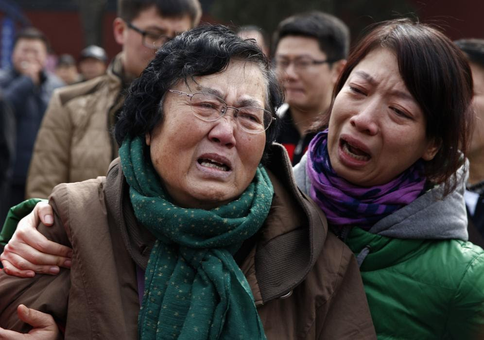 Wang Guohui, mother of Li Zhi, a passenger of the missing flight MH370, cries with daughter-in-law Catherine Gang at a gathering in Beijing
