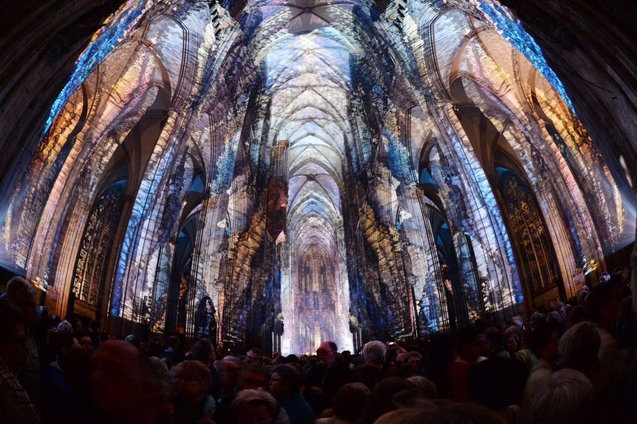 """Visitantes observan la instalación de luz llamada """"lux eucharística"""" dentro de la catedral de Colonia, Alemania, y que forma parte de los eventos del Congreso Eucarístico que se esta desarrollando ahora. (AFP)"""