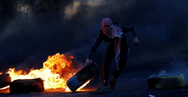 Un palestino sujeta un neumático en llamas durante las protestas producidas tras el reconocimiento de Jerusalén como capital de Israel por parte de Trump./REUTERS