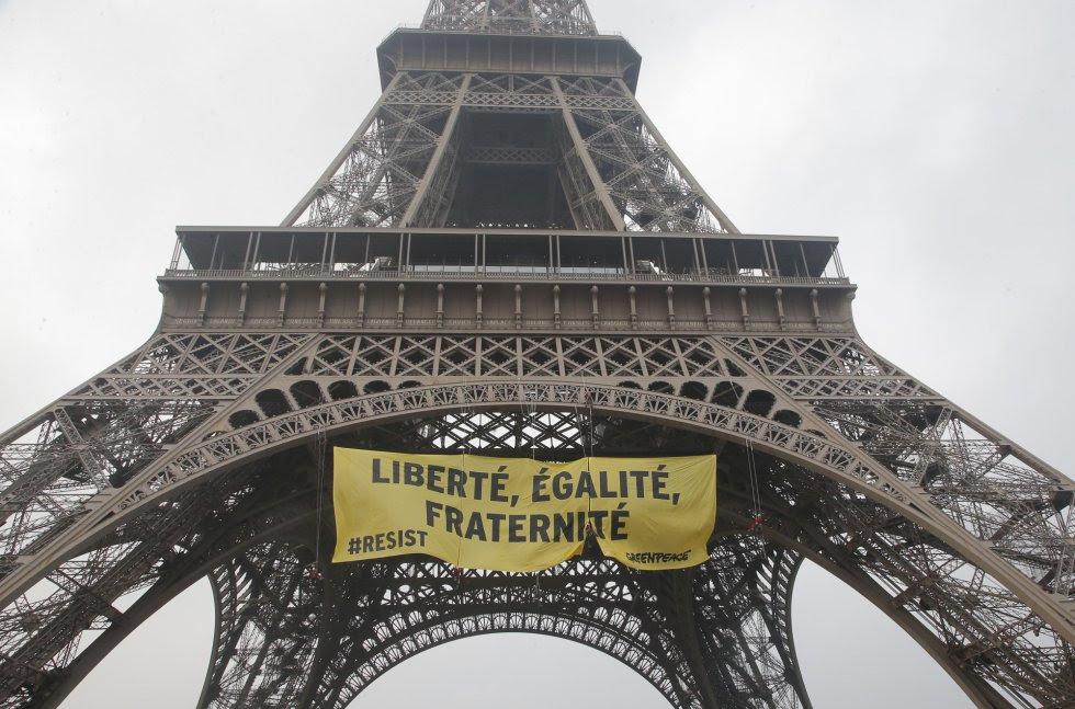 Activistas desplegando la pancarta en la Torre Eiffel.