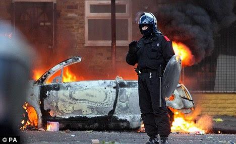 Hands up: A riot officer stands in front of a burning car in Hackney