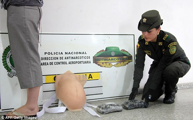 Colombia's Police show Canadian national Ritchie Tabatha Leah (left) after being detained at Bogota airport today, alongside the fake baby bump and 2kgs of cocaine
