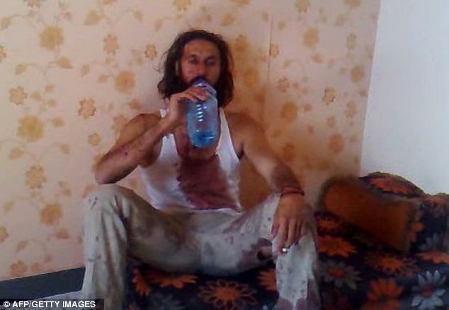 Alive: Mutassim Gaddafi drinks water and smokes a cigarette before his death in Sirte