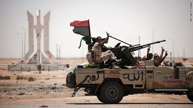 Libyan rebel fighters flash the victory sign as they drive to the frontline on June 11.