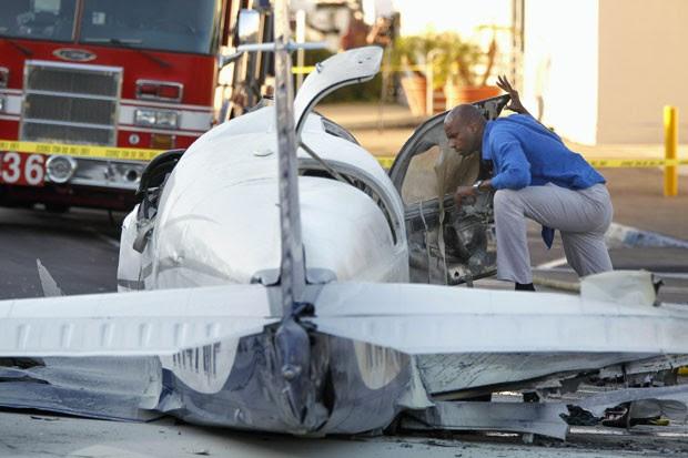 Inspetor de aviação analisa pequeno avião que caiu em estacionamento de shopping em San Diego, nos EUA, nesta quarta-feira (30) (Foto: UT San Diego, Hayne Palmour IV/AP)