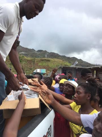 Cooperantes de Oxfam reparten pastillas potabilizadoras de agua y jabón a un grupo de madres de Plain Matin, a una hora y media en coche de Les Cayes, en el sur de Haití.