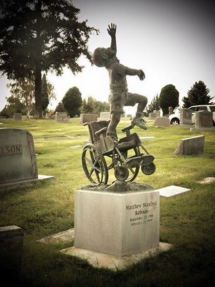 [Photo of a tombstone depicting a boy leaping from his wheel chair]