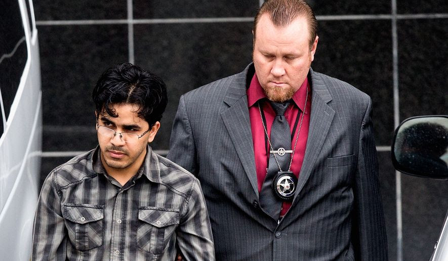 Omar Faraj Saeed Al Hardan is escorted by U.S. Marshals from the Bob Casey Federal Courthouse on Jan. 8 in Houston. (Associated Press)