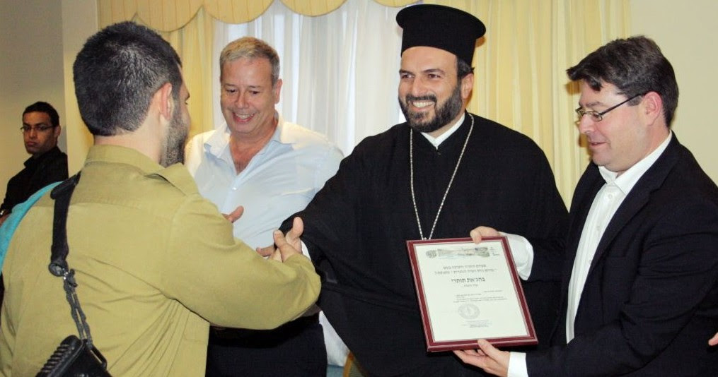 A Christian Arab soldier receiving a certificate of appreciation from Greek Orthodox priest Gabriel Naddaf during a 2013 event in Nazareth (photo credit: courtesy IDF Spokesperson's Unit)