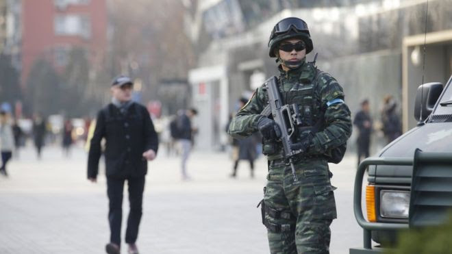 An armed policeman (R) of the Snow Leopard Commando Unit stands guard near a police van at the Sanlitun area, a fashionable location for shopping and dining, in Beijing, China, December 24, 2015