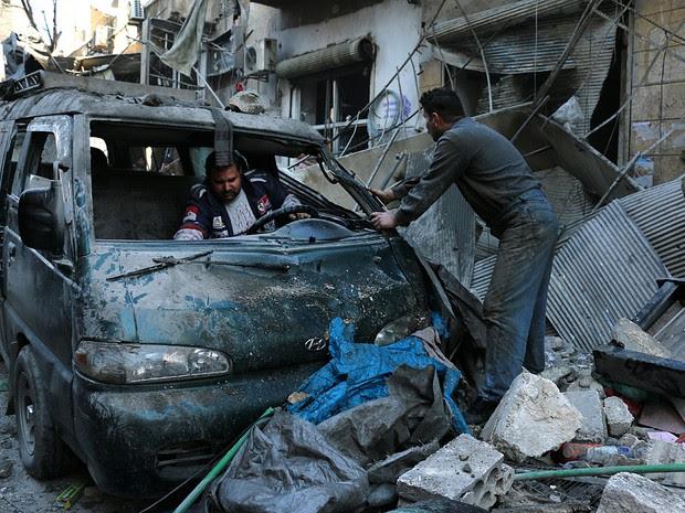 Sírios ispecionam vam em meio a escombros de bombardeio em Aleppo (Foto: Karam Al-Masli/AFP)