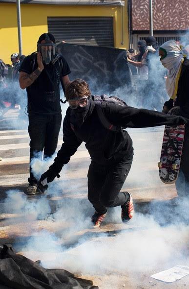 Manifestante com máscara devolve bomba de gás lacrimogêneo em policiais