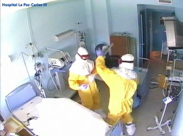 Imagem retirada de vídeo mostra funcionários em roupas especiais limpando o quarto onde o missionário Miguel Pajares foi tratado em Madri (Foto: Madrid Regional Health Authority/AP)