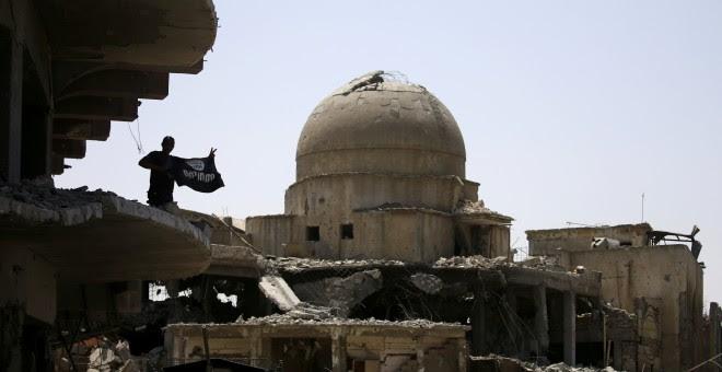Un miembro de las fuerzas iraquíes levanta una bandera del Estado Islámico sobre un edificio destruido en la batalla en Mosul REUTERS/Thaier Al-Sudani