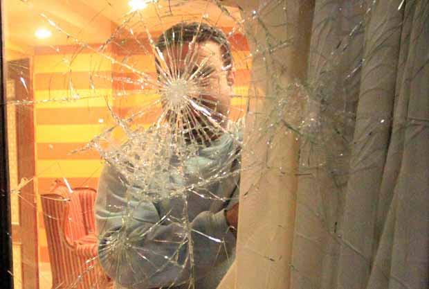 Funcionário da embaixada síria observa estragos após ataque desta sexta-feira (27) no Cairo (Foto: AFP)