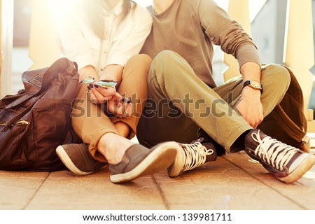 Young couple sitting on the ground in summer. Vintage sunny colors.