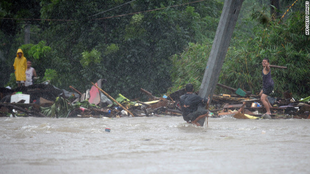 A man clutches a pole in flood waters after a river overflowed following torrential rain in Manila.