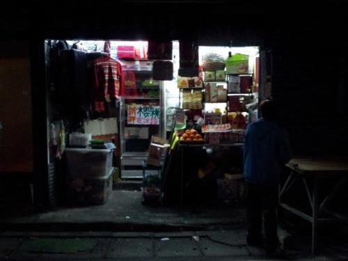 Taipei: A fruit shop at the open market, handily closed up his small shop. (photo: Feb 22, 2013)台北:店仕舞素食屋で食事を終え、超市商場・スーパーでちょこっと買い物をし、公園通りの青空市場の路地をぶらぶらしながら帰路に着きます。夜七時過ぎ、この時間に出ている屋台はほんの二三軒だけです。一軒の果物屋が片づけをしていました。店仕舞です。ここは屋台ではなく、小さな間口と奥行きのない、それでいて屋台と並んで商売をしています。屋台は仕舞い方が重要。小分けにした商品を、一人で運べる重さに仕分けて棚に並べたり、リヤカーに積めるよう要領よく按配すること。一人で片がつけられること。脇で見ていて、なるほどと感心させられました。小型トラックの荷台いっぱいに温室トマトを山積みしているお店。いつも遅くまで路肩に止めています。「一斤ね」とわたし、こちらで一斤は500グラムを意味します。「二十五塊吧」、25元にしとくよとオネーサン。馴染みですから、他に客もいませんので五元おまけしてくれました。わたしは「好的」、あいよと返事。サラダにサンドウィッチに、たまに素食のラーメンの具に、これで一週間持ちます。部屋に戻り、念入りに洗い、熟し加減を確かめます。四分の一は熟れ過ぎです。早めに食さねば…