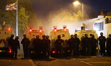 Riot police deploy a water cannon after being attacked by loyalist protesters in Belfast on 13 July