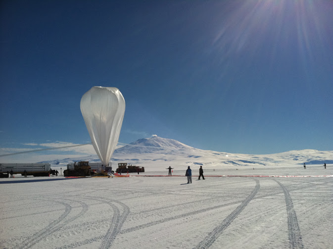 The balloon, ready to launch, dwarfs people and the distant Antarctic peaks across the ice fields under a dazzling blue sky