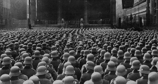 A sea of steel helmets before the Feldherrnhalle in Munich, November 8th, 1935, where thousands of recruits gathered to swear an oath of fealty to Germany's new army flag, which bore the Nazi swastika. Photograph: Keystone/Getty Images