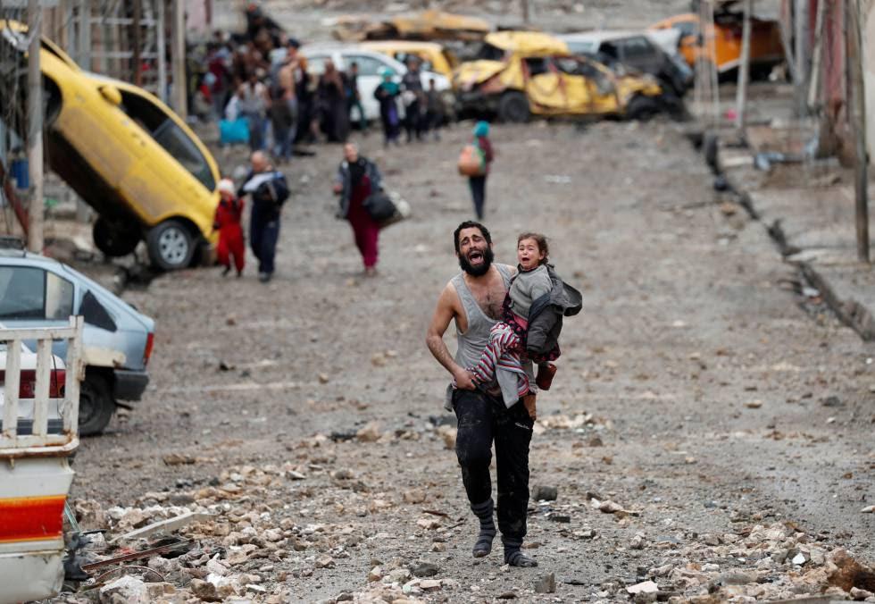 Un hombre huye con su hija de un lugar controlado por el Estado Islámico en Mosul, el sábado