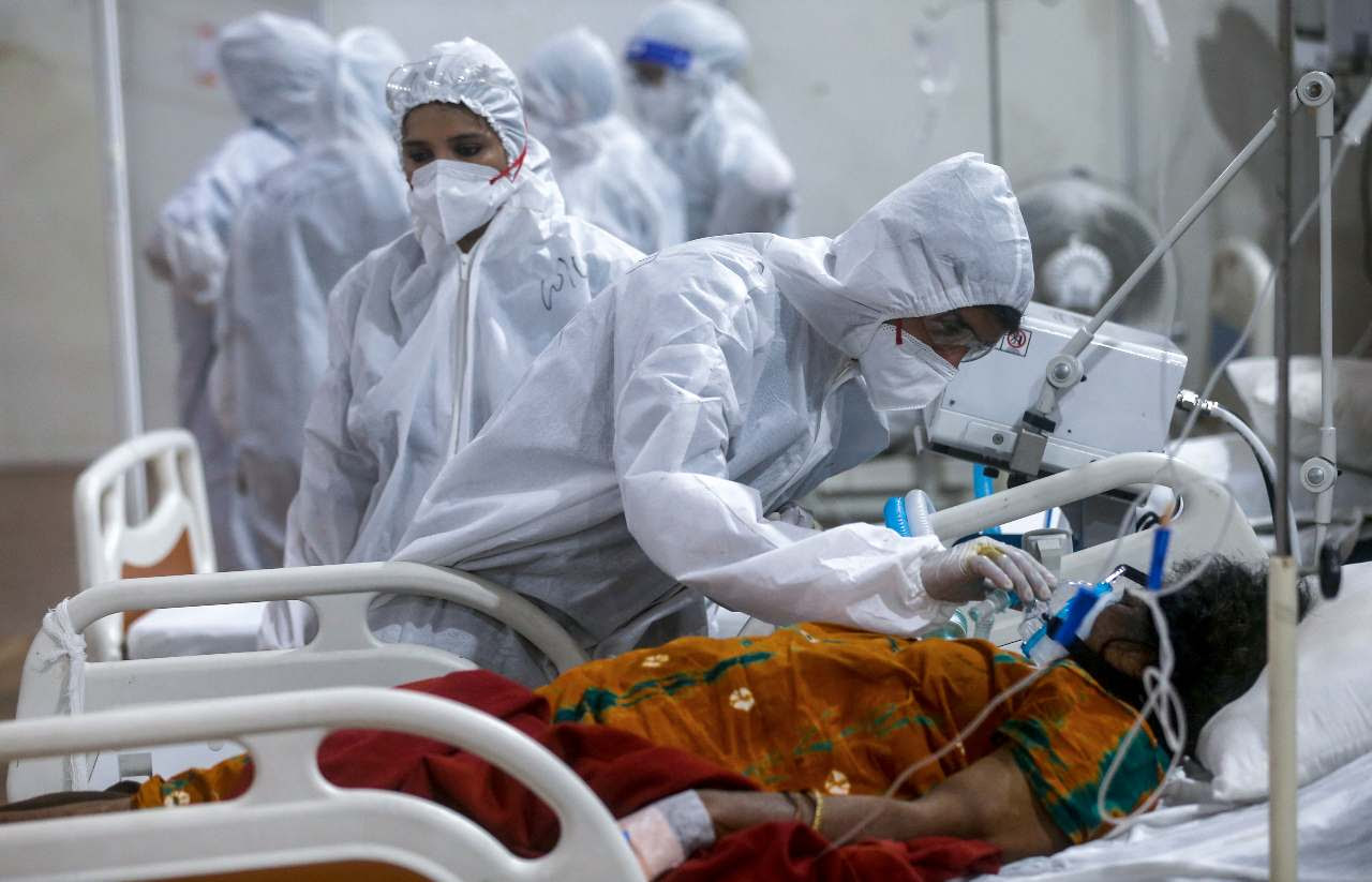 A health worker tries to adjust the oxygen mask of a COVID-19 patient at the BKC field hospital in Mumbai, India, Thursday, May 6, 2021.(AP Photo/Rafiq Maqbool)