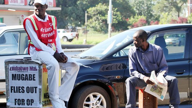 "Men in Harare, Zimbabwe, near a poster with the headline: ""Mugabe flies out for op"" - February 2014"