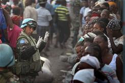A U.N. soldier from Uruguay asks for calm as a long line of women await food at an aid distribution site Wednesday in Port-au-Prince. Some Haitian officials said they would like a say in how aid is distributed.