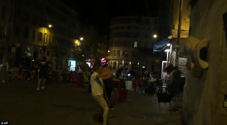 Aggressive: England fans run around outside the Irish bar as concerned police watch on