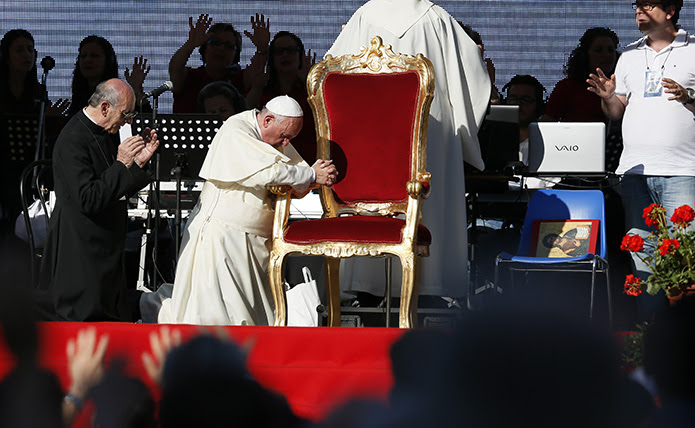 Pope Francis kneels as the crowd prays over him by singing and speaking in tongues during an encounter with more than 50,000 Catholic charismatics at the Olympic Stadium in Rome June 1.