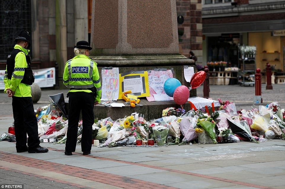 Police officers stand next to floral tributes left for the victims of an attack on concert goers at Manchester Arena, in St Ann's Square,  Manchester, today