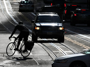 A bicyclist rides his bike down the street in San Francisco.