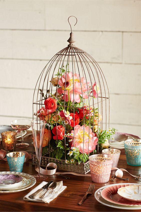 ein vintage-Käfig mit üppigen roten und rosa Blüten und grün für eine bunte Hochzeit