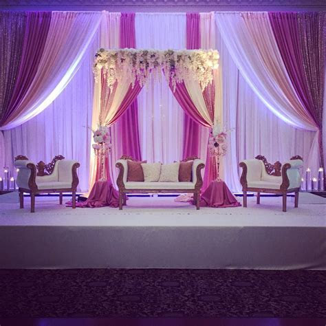 Blush pink reception backdrop with florals.   Indian