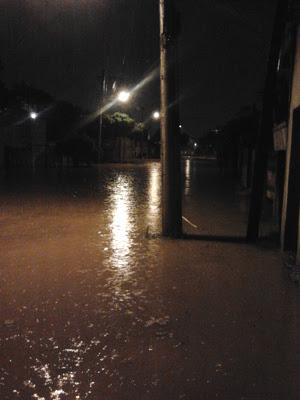 Na Rua Barão de Indaiá, o nível da água estava atingindo a cintura dos pedestres. (Foto: Graziela Pereira de Almeida/VC no G1)