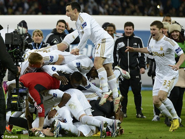 Bundle: Swansea City players pile up in celebration at Wembley
