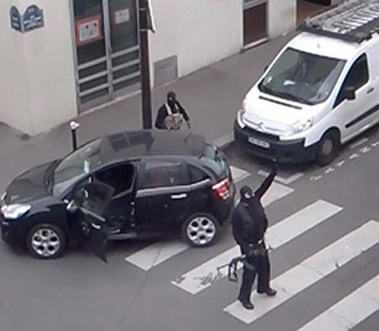 Gunmen gesture as they return to their car after the attack outside the offices of French satirical weekly newspaper Charlie Hebdo (seen at rear) in this still image taken from amateur video shot in Paris January 7, 2015. REUTERS/Reuters TV
