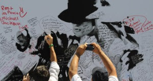 Fans leave messages on a Michael Jackson poster outside The Staple Center. Photo: Getty