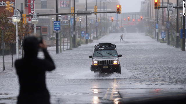 A member of the press takes a photo of a flooded street on Monday in Atlantic City, New Jersey.