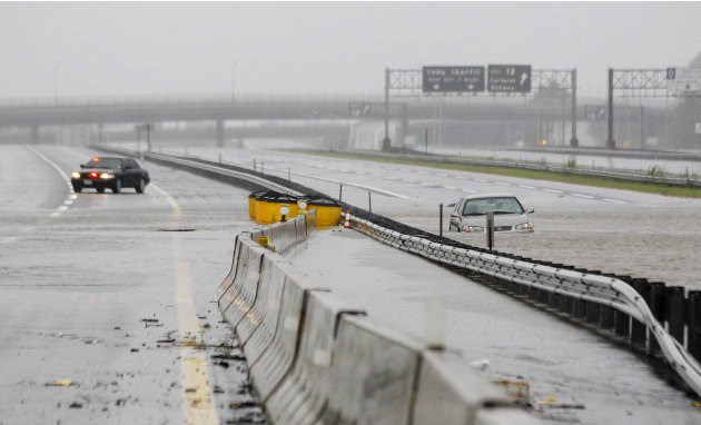 An abandoned car is half-submerged in a southbound lane of the New Jersey Turnpike near exit 12 as floodwaters from Hurricane Irene cover the road Sunday, Aug. 28, 2011, in Carteret, N.J. (AP Photo/Ju