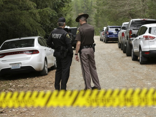 Mason County Sheriff's Chief Criminal Deputies Russ Osterhout, left, and Ryan Spurling, right, stand on a road near the scene of a fatal shooting Friday, Feb. 26, 2016, near Belfair, Wash. A gunman who killed four people in rural Washington state called a (Foto: Ted S. Warren/AP)