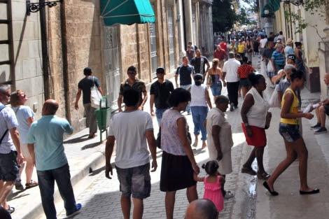 Varias personas caminan por una calle de La Habana. | Efe
