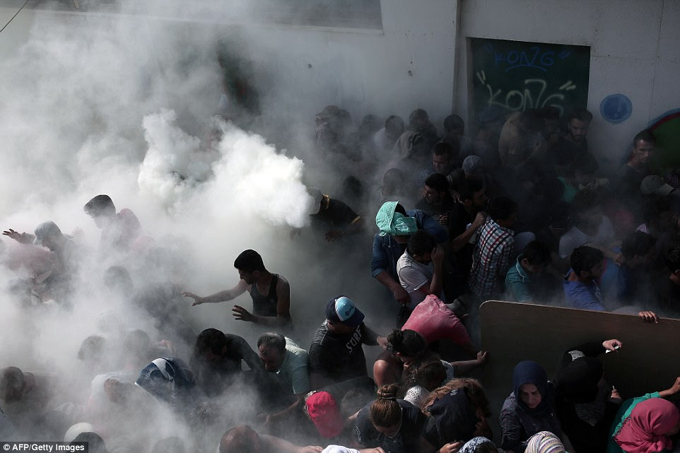 Running in panic: Policemen try to disperse hundreds of migrants by spraying them with fire extinguishers this morning