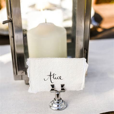 four small silver name card table number holders by the