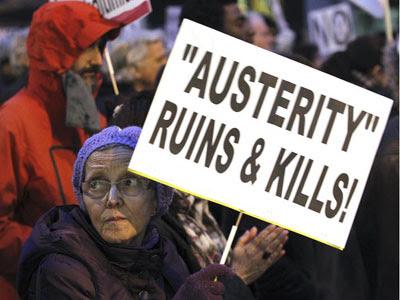 Una mujer porta una pancarta con el lema en inglés 'Austeridad arruina y mata¡', en la manifestación del colectivo Re-acciona en Madrid contra las políticas de la UE/EFE