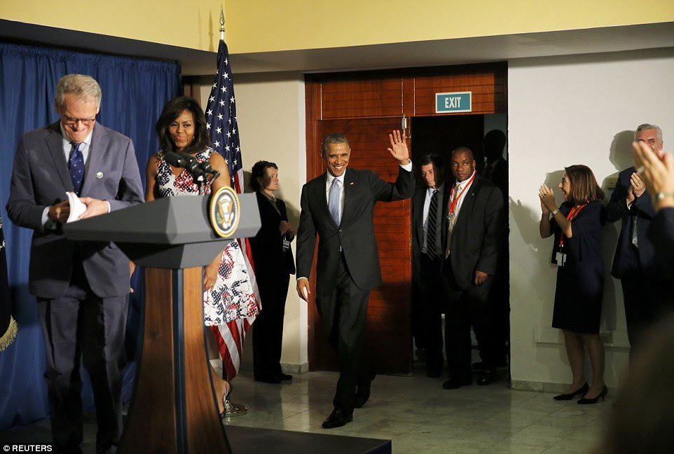 President Barack Obama waves as he and his wife Michelle walk into a room with the U.S. ambassador to Cuba, Jeffrey DeLaurentis (left), soon after the Obamas arrived in Cuba